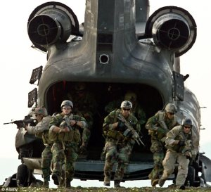 Navy SEALS emerging from a Chinook helicopter